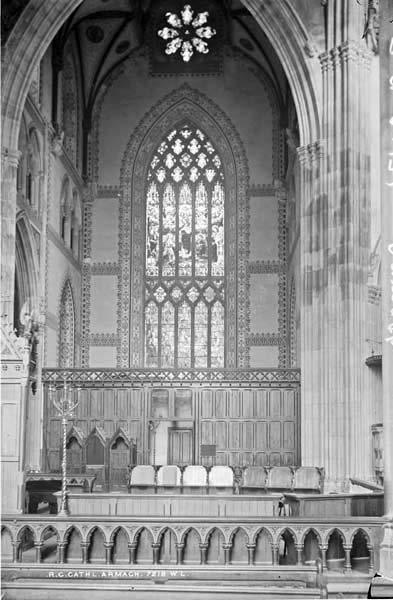 "The south transept as completed by McCarthy showing the temporary sacristy behind a wooden screen and the ""Puginesque"" historicist stencilled decoration to the walls which was later covered in mosaic."